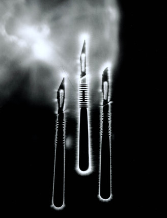 Kirlian photograph of three scalpels.