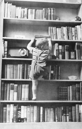 Child climbing a bookshelf, c 1977.