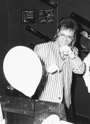 Cliff Richard punching a balloon, c 1970s.
