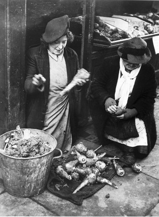 Greengrocer cleaning soil off parsnips, 13 January 1945.