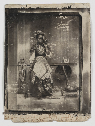 Woman in traditional costume with musical instruments, 1866.