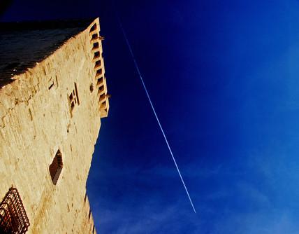 Vapour trail over the Palais des Papes, Avignon, France, 2004.