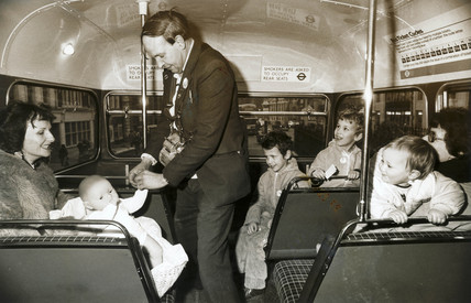 Bus conductor collecting a fare from a doll, 1982.