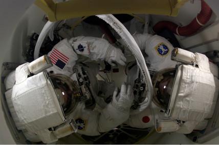 Astronauts preparing for a spacewalk, August 2005.