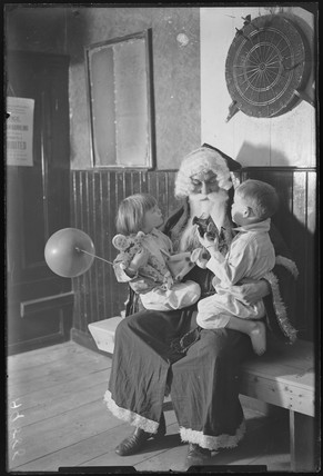 Father Christmas with two children, 1932.