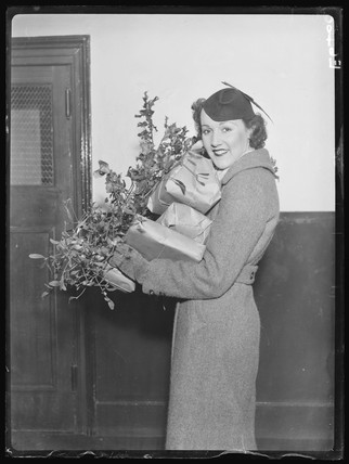 A young woman loaded with Christmas parcels, holly and mistletoe, 1935.