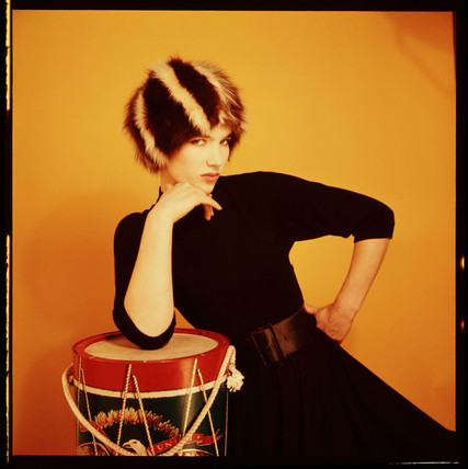 Woman in a fur har, leaning on a drum, 1960s.