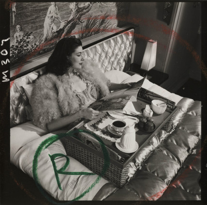 Woman having breakfast in bed, 1950s.