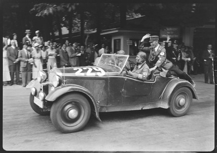 Swastika-wearing men in a motor racing car, Germany, c 1934.