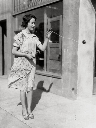 Girl playing yo-yo on a street corner, 1930s.