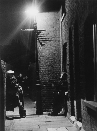 Men loitering in the street at night in a slum area of London, 1937.