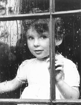 Boy looking through window, November 1949.