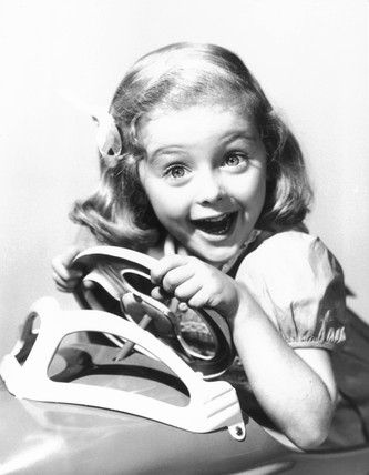 Young girl in a toy car, USA, 1940s. Young