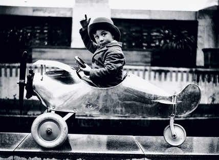 Boy sitting in a toy aeroplane, Selfridges, 1931.