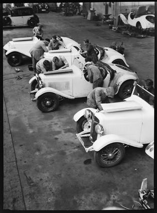 Mechanics work on the engines of three motor racing cars, Germany, c 1934.