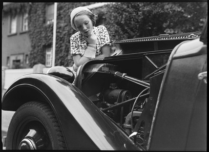 A woman looks at the engine of an Adler motor car, Germany, c 1934.