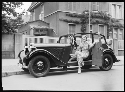 A woman sits in the door of an Adler motor car, c 1934.