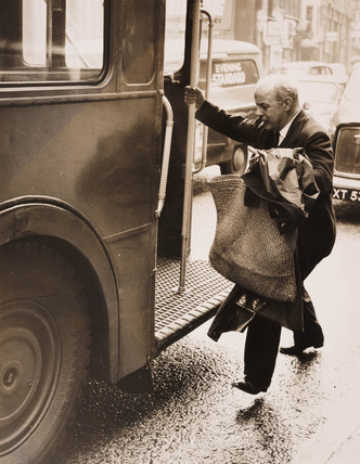 John Betjeman jumping onto a bus, London, 29 March 1962.
