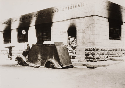 Burnt-out armoured car outside Barclays Bank, Hebron, 1938.