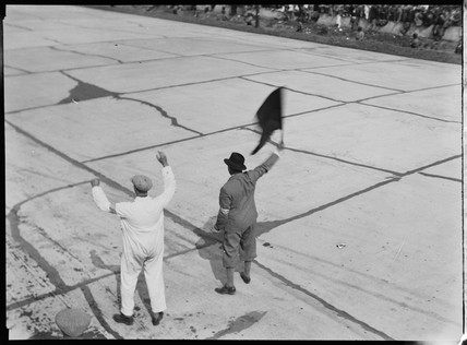 Waving the finishing flag at a motor race, 1930s.