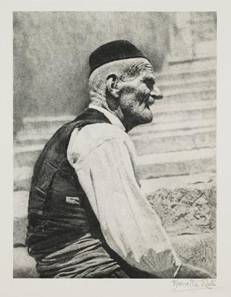 Elderly man seated on steps.;