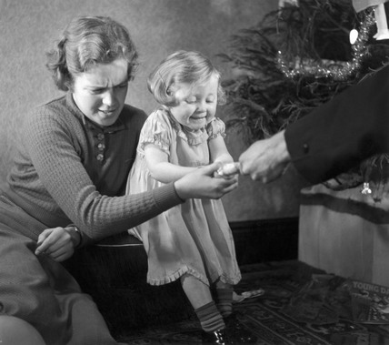 Mother and child pulling a Christmas cracke
