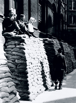 Men resting on top of piles of sandbags, WWII, London, 4 September 1939.