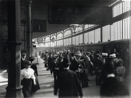 Railway travellers on a platform, c 1900s.
