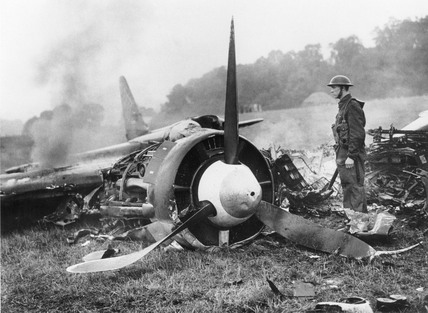 Soldier guards the burning remains of a Junkers 88, 4 October 1940.