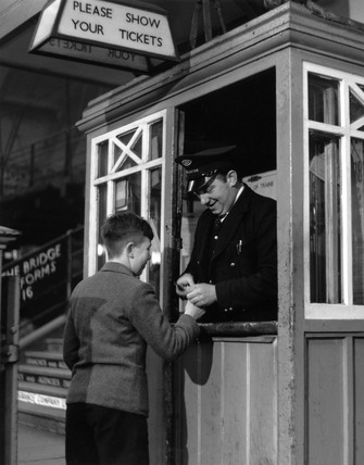 Small boy at York station having his ticket clipped, York, November 1951.