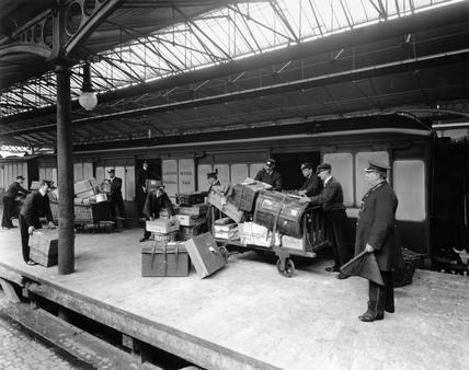 Porters loading passengers' luggage, c 1913.