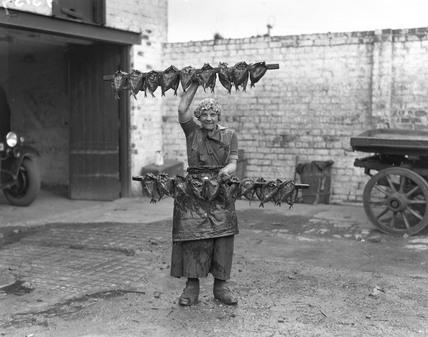 Kipper girl displaying smoked kippers.