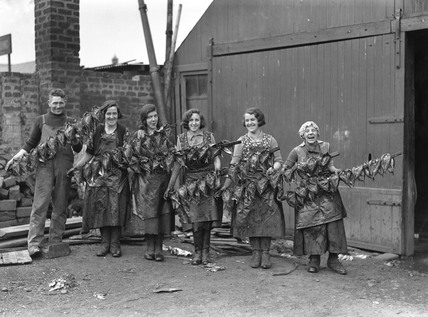 Kipper girls displaying smoked kippers.