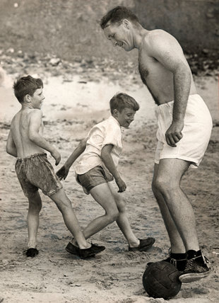 Jock Stein, Scottish footballer, playing football with two boys, 1955.