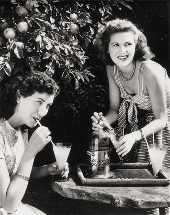 Two young women enjoying a summer drink, 1945-1955.