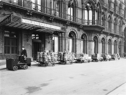 Porter driving a goods vehicle with a train of goods trolleys, 1920.