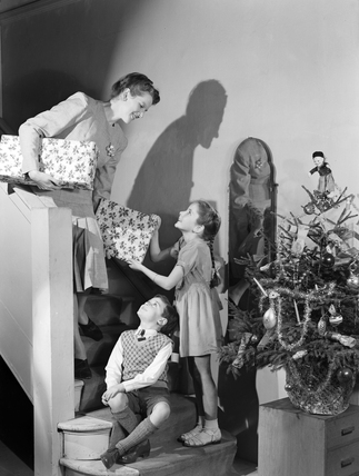 Woman and two children carrying Christmas presents, c 1948.