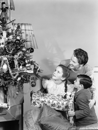 Woman and two children looking at a Christmas tree, c 1948.