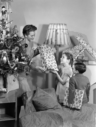 Woman giving Christmas presents to children, c 1948.