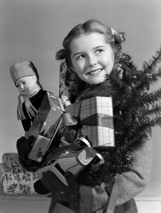 Young girl carrying an armful of Christmas presents, c 1950.