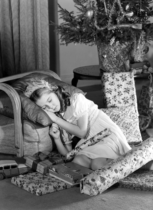 Little girl asleep under Christmas tree, c 1950.