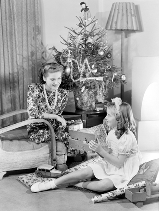 Woman and girl looking at Christmas presents, c 1950.
