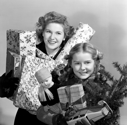 Woman and child carrying Christmas presents, 1948.