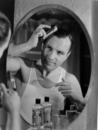 Man brushing his hair in a mirror, c 1950s.