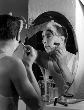 Man shaving using a razor in a mirror, c 1950s.