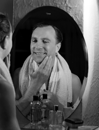 Man looking into a mirror admiring his face after shaving, c 1950s.