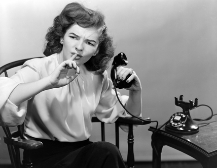 Woman using the telephone asking for quiet, c 1950.