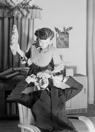 Woman surprising a man with a Christmas present, c 1950.
