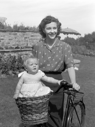 Woman on a bicycle with a baby riding in a basket, c 1955
