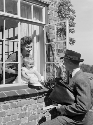 Man waving goodbye to a woman and baby, 1951,